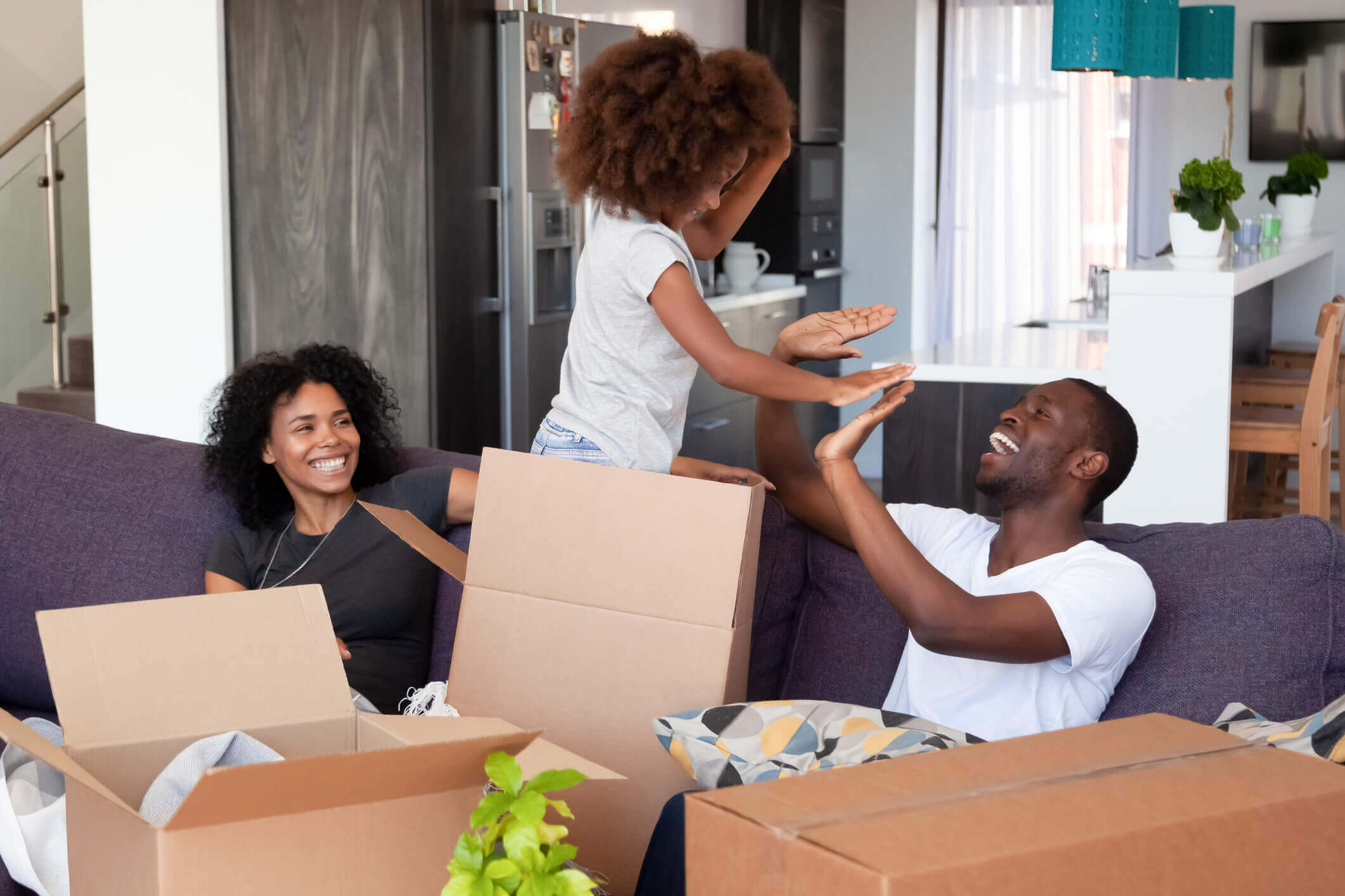 Família feliz reunida em sala com caixas de mudança | Blog da Tenda