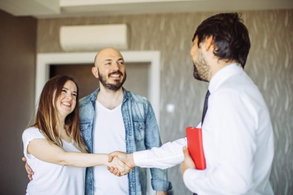 Abraçados, casal sorri enquanto a mulher aperta as mãos de um corretor | Motivos para sair do aluguel | Guia da Tenda | Blog da Tenda