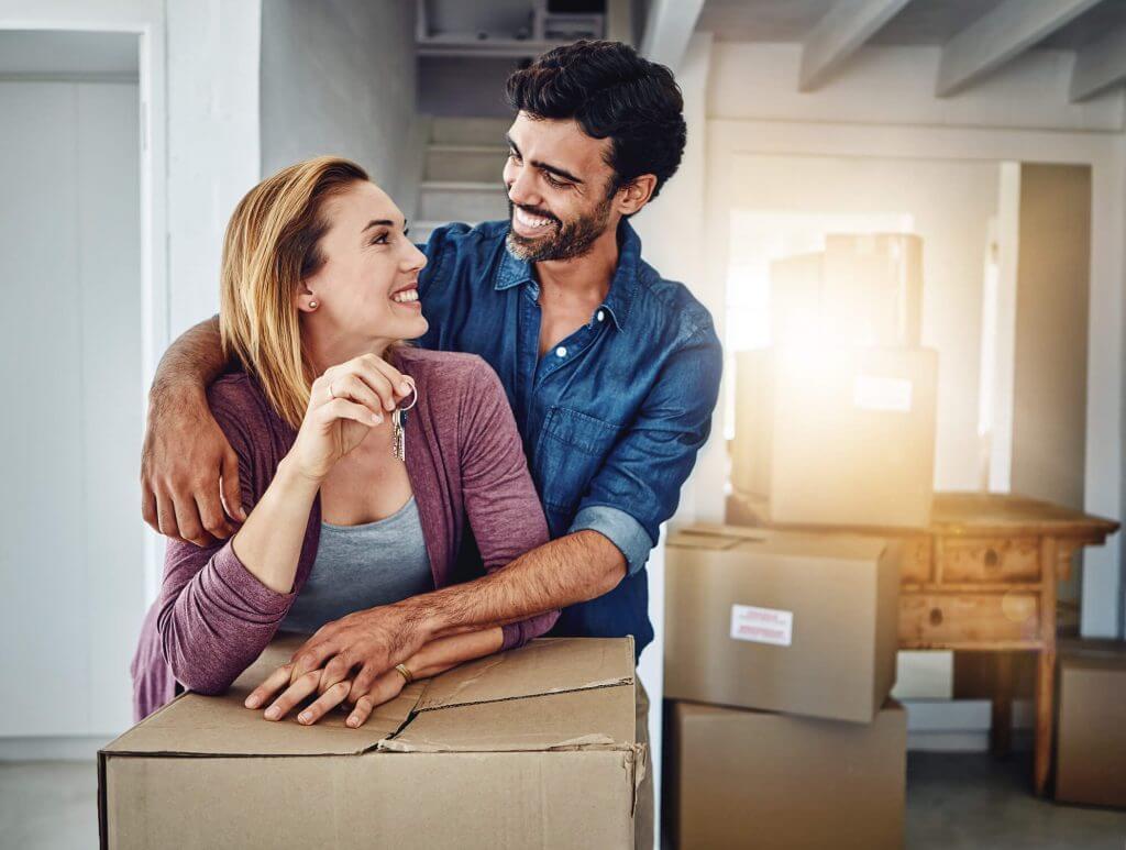 Em uma sala cheia de caixas de papelão, homem e mulher sorriem enquanto mulher segura uma chave | Motivos para sair do aluguel | Guia da Tenda | Blog da Tenda