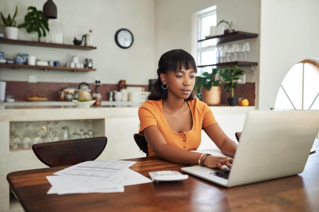 Mulher em uma mesa com papéis lê informações em um notebook | Construtora Tenda é confiável | Guia da Tenda | Blog da Tenda