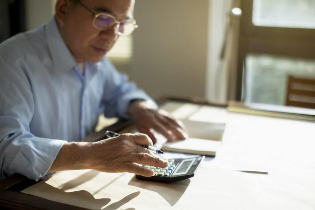 Foto de um homem idoso usando uma calculadora   O que é subsídio?   Minha Casa Minha Vida   Blog da Tenda