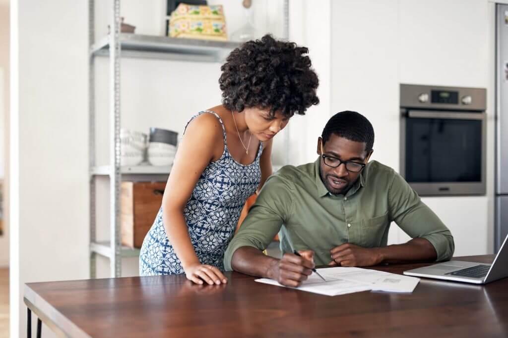 Em uma mesa, homem e mulher avaliam documentos ao lado de um notebook | Valor do condomínio | Morar em Condomínio | Blog da Tenda
