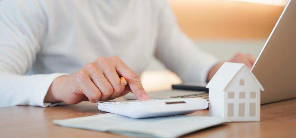 ´Foto de um homem usando uma calculadora e um notebook | Composição de renda | Guia da Tenda | Blog da Tenda