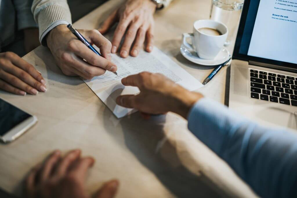 Foto de um homem assinando um contrato | Composição de renda | Guia da Tenda | Blog da Tenda