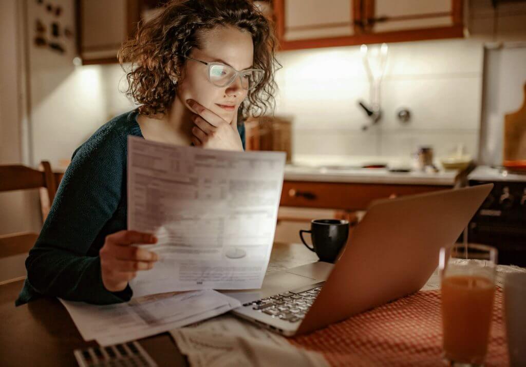 Sentada em uma mesa, mulher segura documento enquanto avalia informações no notebook | Simulador de Imóvel | Guia da Tenda | Blog da Tenda