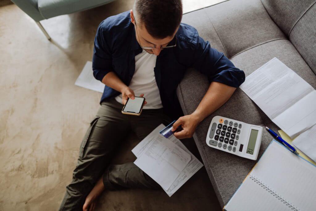 Homem fazendo contas sentado no chão de casa   Valor das parcelas  Guia da Tenda   Blog da Tenda