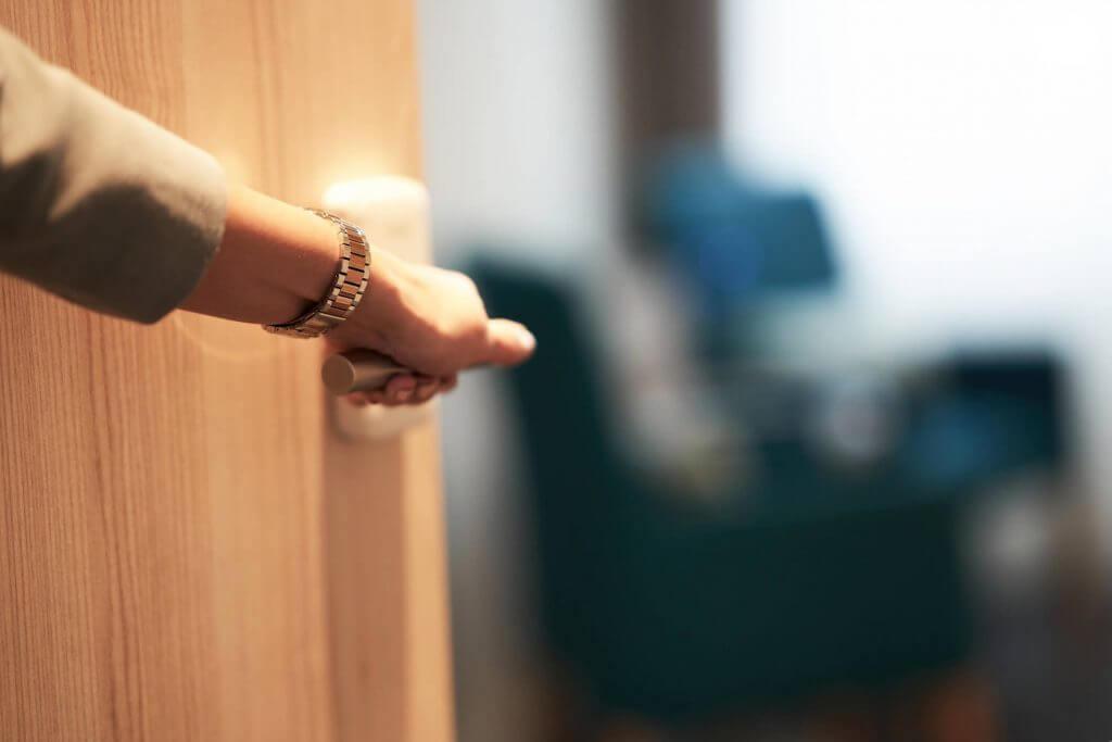 Mão de uma mulher abrindo uma porta | Subsídio habitacional | Minha Casa Minha Vida | Blog da Tenda
