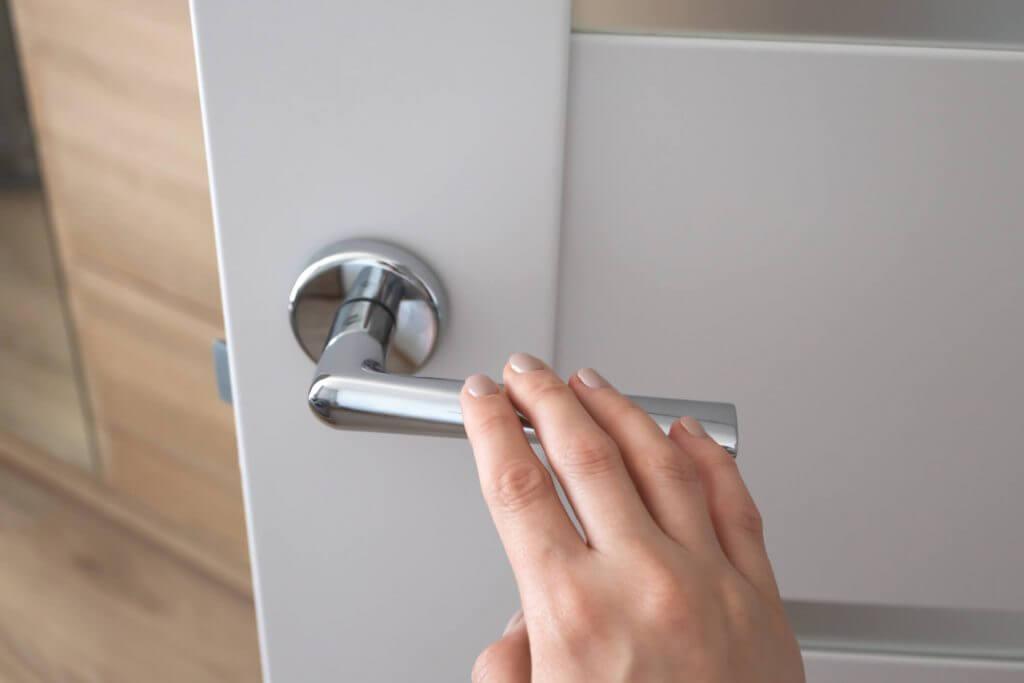 Foto de uma mão feminina abrindo uma porta | Financiamento de imóvel | Guia da Tenda | Blog da Tenda