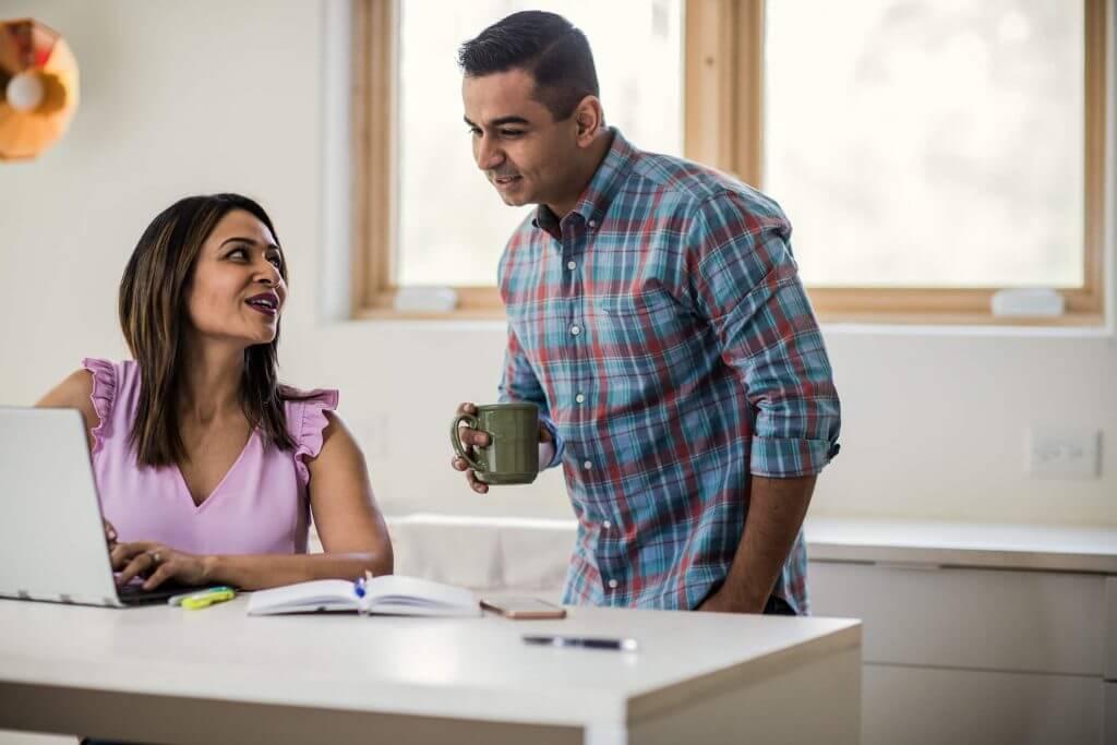 Mulher mexendo em um notebook enquanto conversa com um homem | Financiamento de imóvel | Guia da Tenda | Blog da Tenda