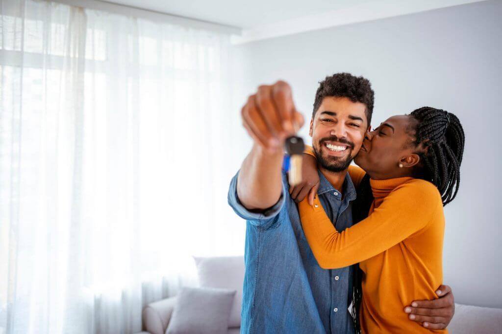 Em uma sala, homem sorri e segura chave enquanto mulher o abraça | Comprando imóvel com FGTS | Guia da Tenda | Blog da Tenda