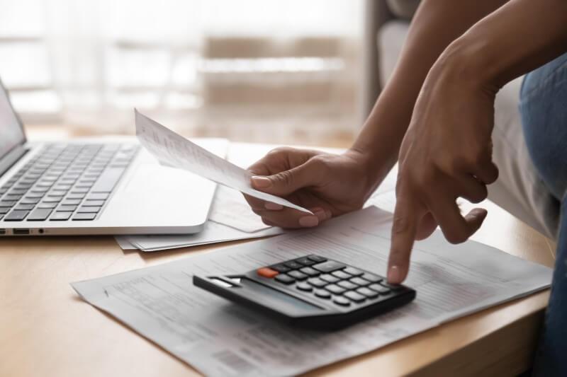 Foto de uma pessoa usando calculadora | Como ser aprovado no financiamento | Blog da Tenda