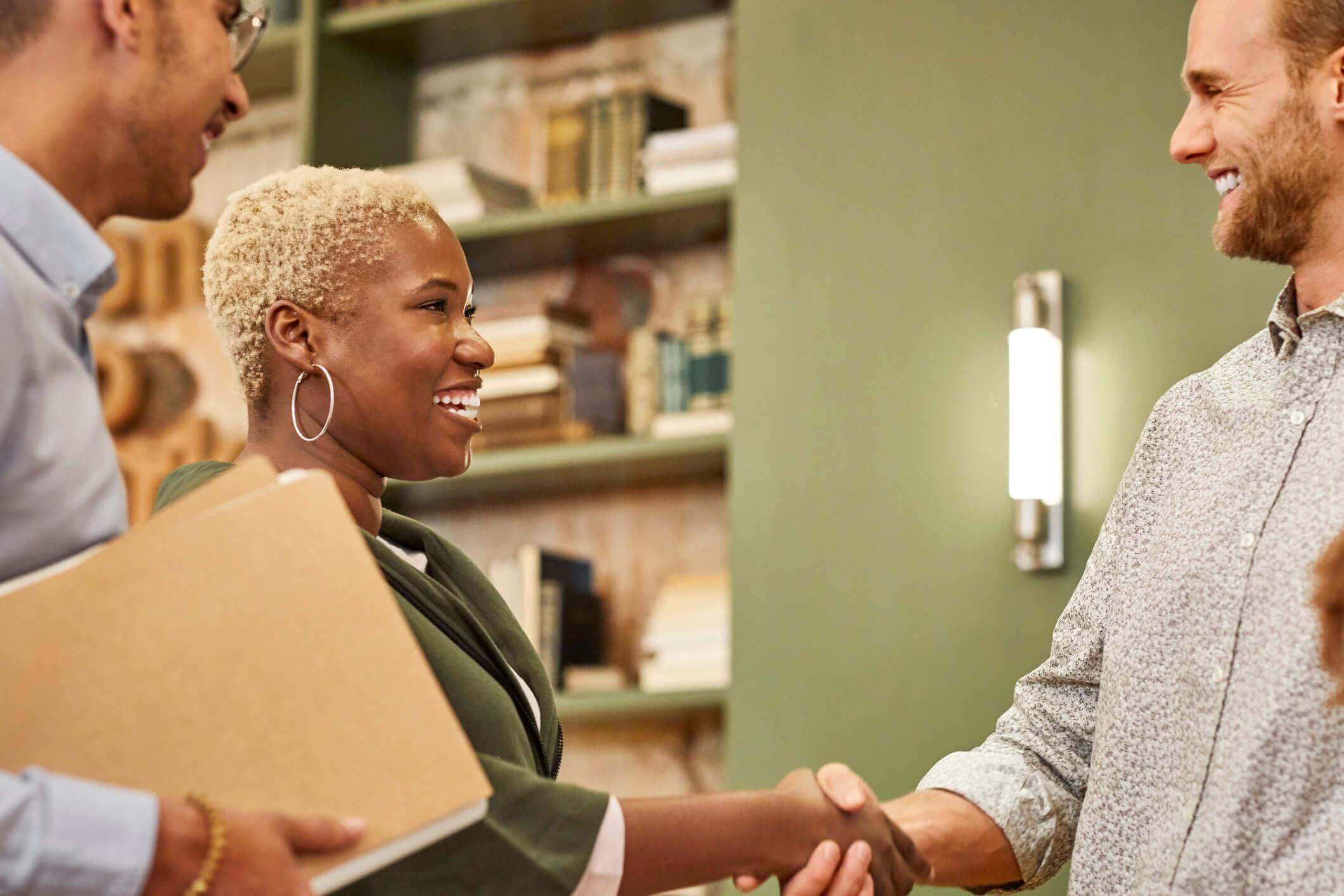 Mulher e homem apertam as mãos e sorriem | Como ser aprovado no financiamento | Guia da Tenda | Blog da Tenda