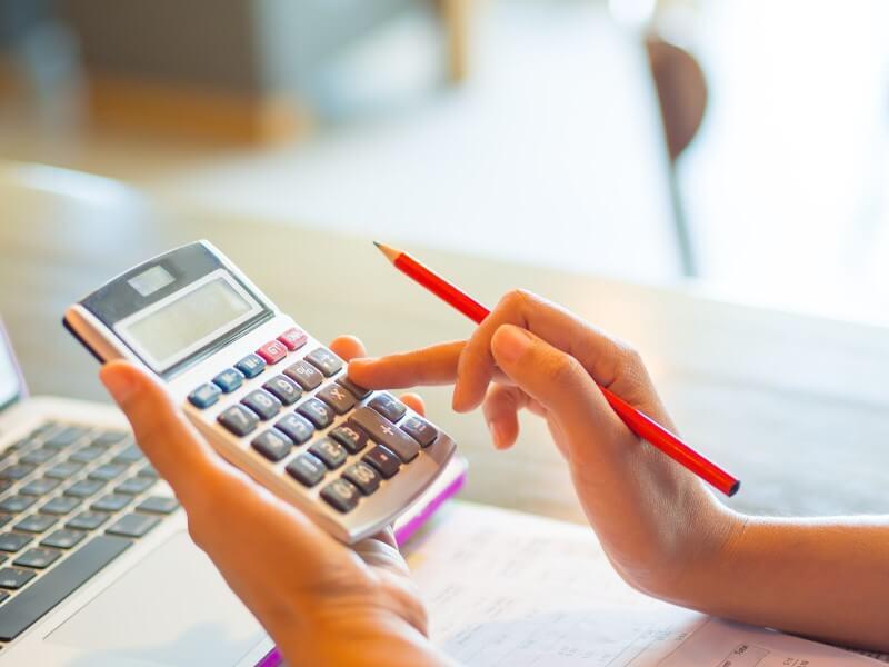 Foto de mãos femininas usando uma calculadora | Financiamento atrasado | Guia da Tenda | Blog da Tenda