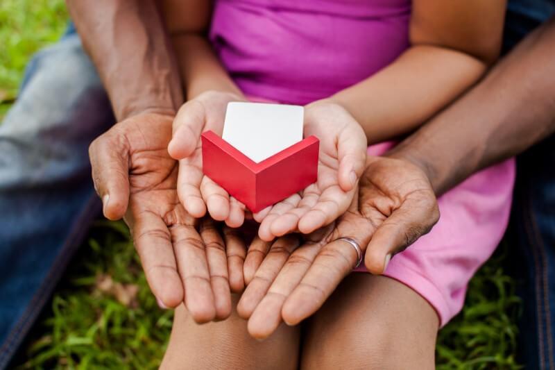 Foto com foco em mãos segurando uma casa em miniatura | Programa Casa Verde e Amarela | Minha Casa Minha Vida | Blog da Tenda