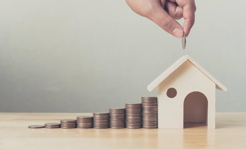 Foto de moedas e uma miniatura de casa   Guia para quitar dívidas   Economize   Blog da Tenda