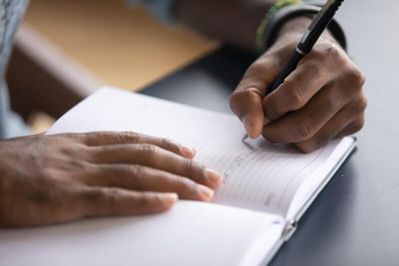 Foto de um homem escrevendo em um caderno   Guia para quitar dívidas   Blog da Tenda