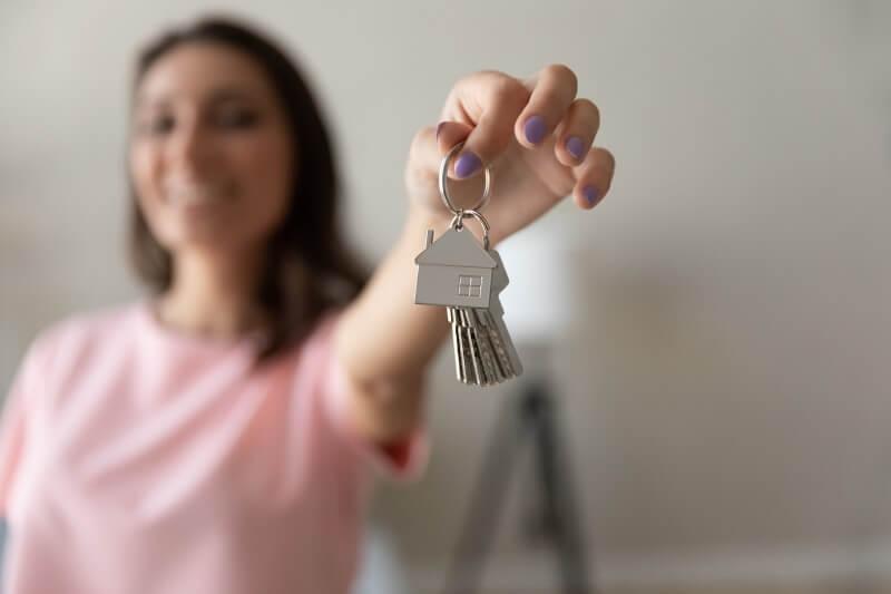 Foto de uma mulher segurando as chaves da casa própria | Idade ideal para comprar um imóvel | Guia da Tenda | Blog da Tenda