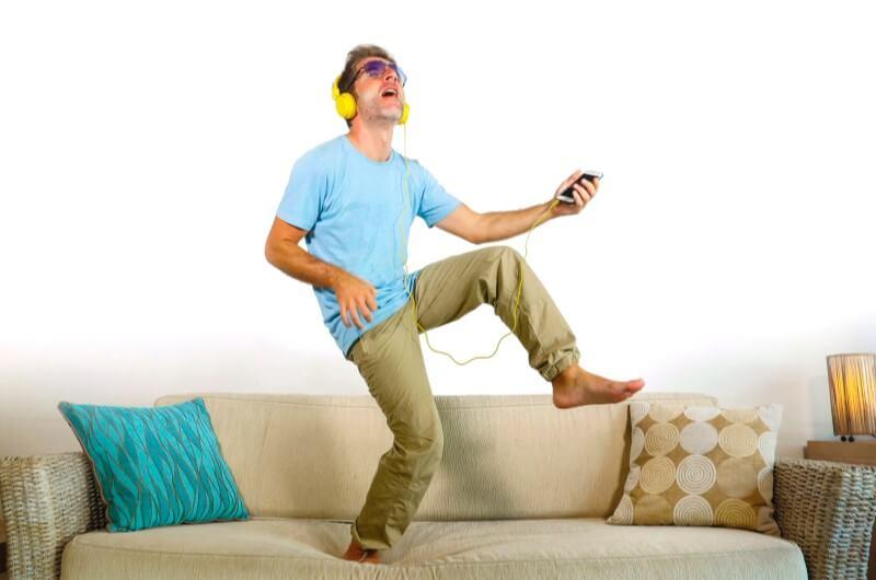 Imagem de homem ouvindo música em cima do sofá   Guia para morar sozinho   Guia da Tenda   Blog da Tenda