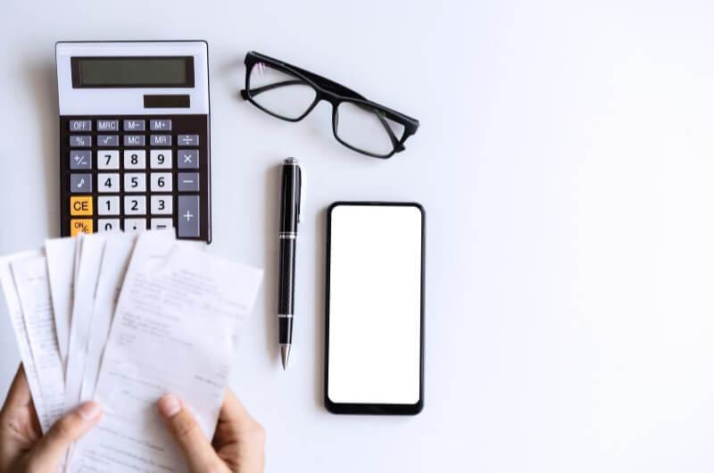 Imagem de mãos de mulher segurando recibos, ao lado de uma calculadora, óculos e celular | Aplicativos de planejamento financeiro | Economize | Blog da Tenda