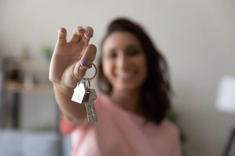 Imagem de uma mulher sorrindo segurando chaves   Guia para morar sozinho   Guia da Tenda   Blog da Tenda