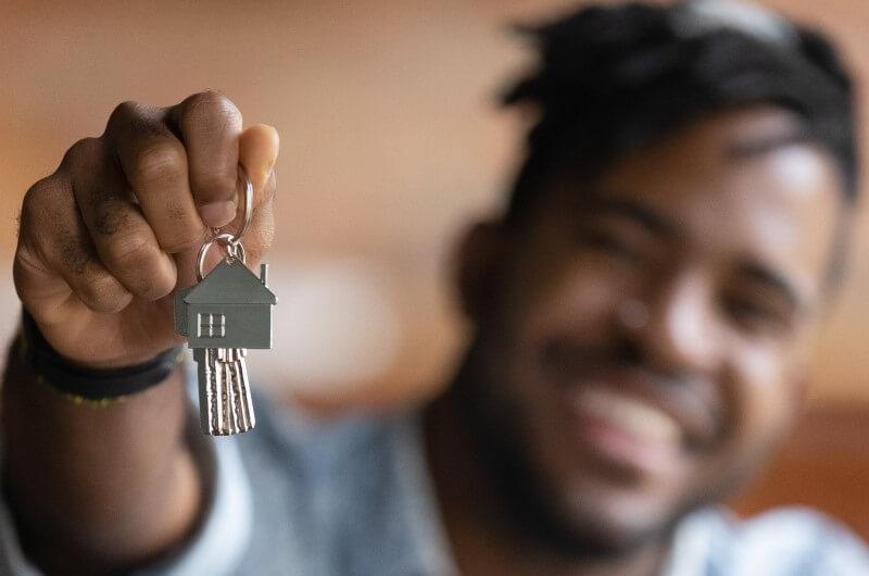Foto de um homem sorrindo segurando chaves | Como utilizar o dinheiro do FGTS | Guia da Tenda | Blog da Tenda