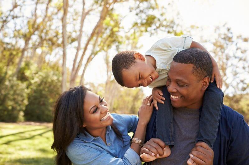 Casal e criança se divertindo ao ar livre | O que é a AGI | Guia da Tenda | Blog da Tenda