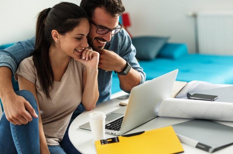 Casal olhando para tela do notebook | Comprar apartamento online | Blog da Tenda