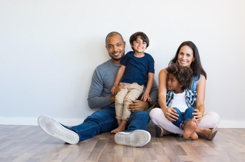 Casal e duas crianças sorrindo sentados no chão   Morar em Condomínio   Blog da Tenda