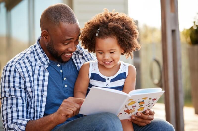 Pai lendo para criança   Livros de educação financeira   Economize   Blog da Tenda