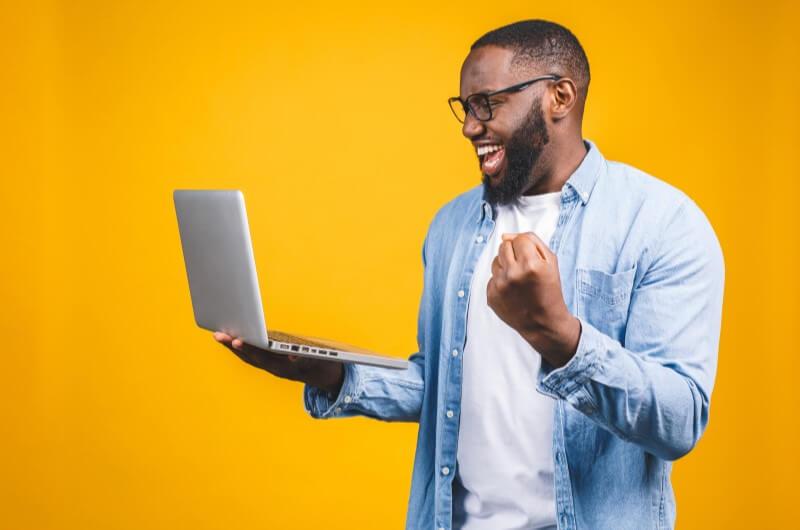 Imagem de um homem comemorando enquanto segura um notebook | Assinatura de contrato online | Guia da Tenda | Blog da Tenda