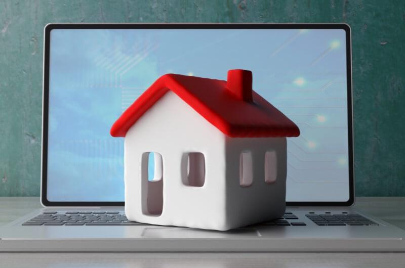 Miniatura de casa em cima de notebook | Diferenças entre o Casa Verde e Amarela e o Minha Casa Minha Vida | Minha Casa Minha Vida | Blog da Tenda