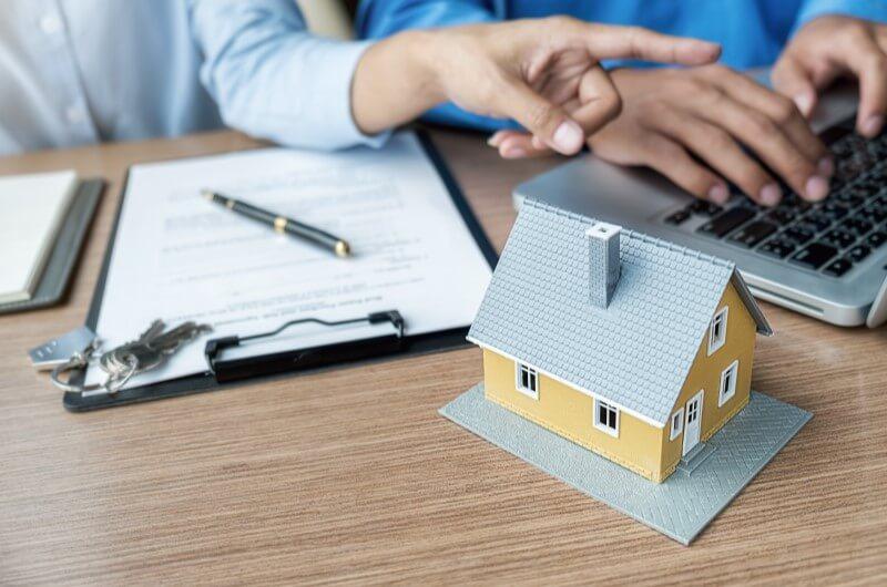 Imagem de duas pessoas mexendo no notebook ao lado de uma casa em miniatura | Guia para comprar a casa própria | Guia da Tenda | Blog da Tenda
