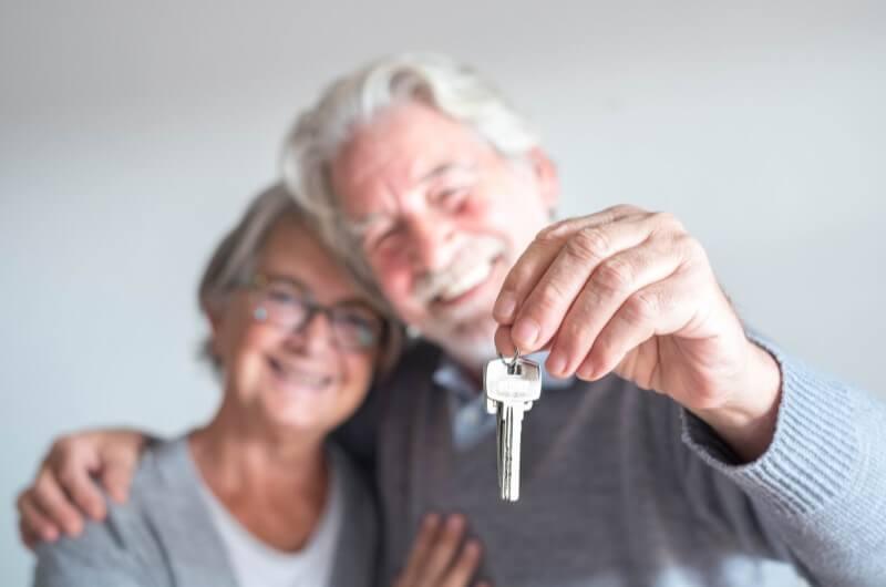 Casal de idosos segurando chaves | idade para comprar imóvel | Guia da Tenda | Blog da Tenda