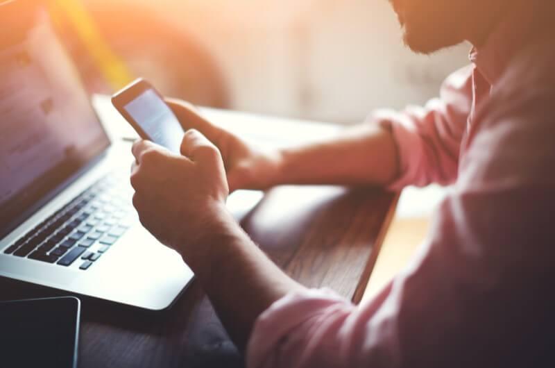 Imagem de um homem utilizando o celular e o notebook | Assinatura de contrato online | Guia da Tenda | Blog da Tenda